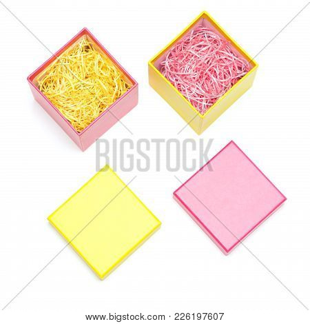 Two Open Colored Gift Boxes Filled With Decorative Shavings On White Background