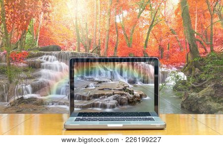 Conceptual Image Of A Computer Laptop On Beautiful Waterfall With Soft Focus And Rainbow In The Fore