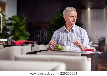 Healthy Food. Wistful Pleasant Mature Man Sitting While Turning From Camera And Holding Fork