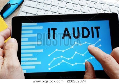 Man Holding It Audit Report In A Tablet.
