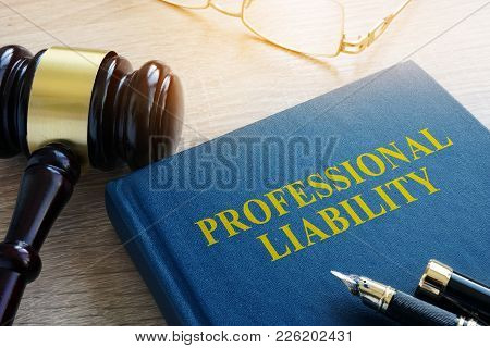Professional Liability And Gavel On A Court Table.