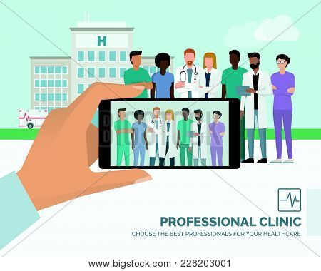 Professional Medical Staff And Doctor Posing Together At The Hospital, A Man Is Taking A Picture Usi