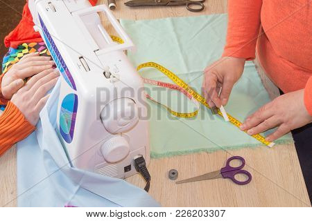 Hands Woman Tailor Working. Woman Hand On Sewing Machine.dressmaker Work On The Sewing Machine. Garm