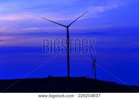 Silhouette Wind Turbine Farm Over Moutain With Twilight Sky And White Cloud