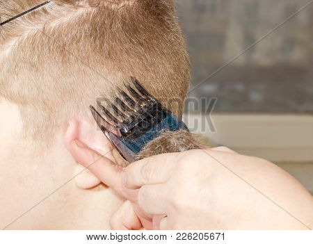 Lateral Part Of Head Of Young Man During Hair Shearing Around The Ear By Means Of Electric Hair Clip