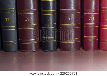 Fragment Of Several Black, Cerise And Red Book Spines Of The Old Tomes Of The Collected Works In Lea