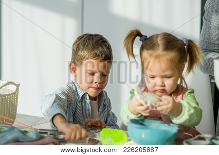 Two Small Children Prepare Something From The Dough. A Boy And A Girl Are Sitting At The Kitchen Tab
