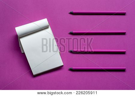 Top View Notepad With Pencils And Copy Space On Pink Paper Background .