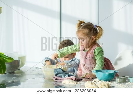 Two Children Are Cooking Something From The Dough. In The Hands Of A Little Girl A Whisk. The Face I
