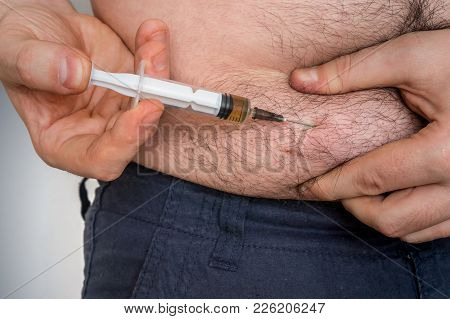 Diabetic Man With Syringe Inject Insulin To His Belly - Diabetes Concept