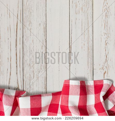 red checkered picnic tablecloth on white wood table