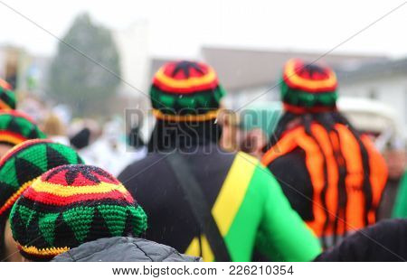 People With Jamaica Caps At Carnival Procession, Rear View