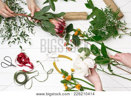 Female Florist Making Beautiful Bouquet At Flower Shop. The White Wooden Florist Workplace. Top View