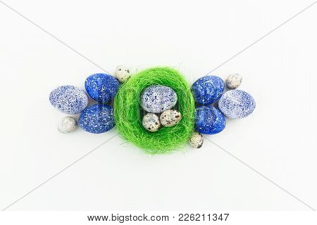 Blue Speckled Easter Eggs And Quail Eggs In Nest On White Background. Flat Lay, Top View. Happy East