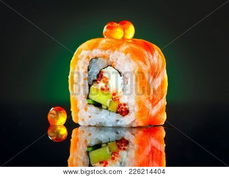 Sushi roll japanese food over black background. California Sushi roll with salmon, vegetables, flying fish roe and caviar closeup. Japan restaurant menu.