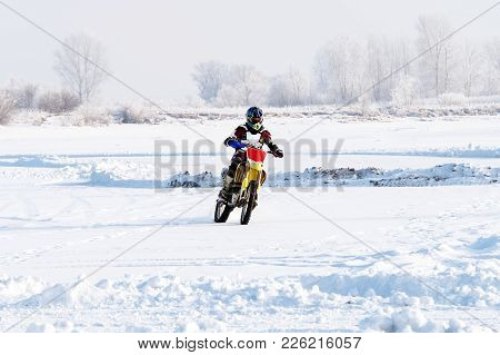 Closeup Man Biker Rides A Motorcycle On A Snowy Hill During Winter Motocross. Extreme Biker Rides Th