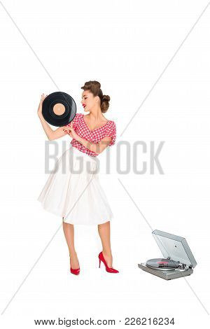 Woman In Pin Up Style Clothing With Vinyl Record Standing Near Phonograph Isolated On White