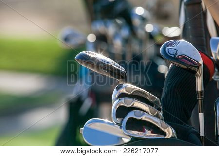 Golf Clubs Glistening In The Sunlight. A Golf Bag Full Of Clubs. Golf Club Heads.