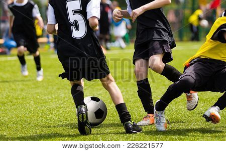 Soccer Players Competing For The Ball. Primary School Football Game. Soccer Tackle. Youth Soccer Tea