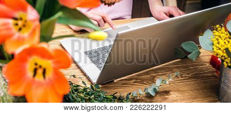 Florist Working In Modern Flower Shop On Laptop . Young Woman Entrepreneur With Her Own Business.
