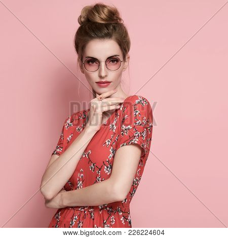 Beautiful Girl In Summer Floral Dress Smiling. Fashion Young Woman, Trendy Sunglasses. Studio Portra