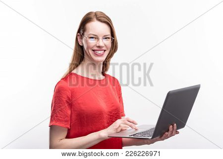 My Device. Gorgeous Ginger-haired Young Woman In A Red Blouse Holding A Laptop And Posing With It Ag