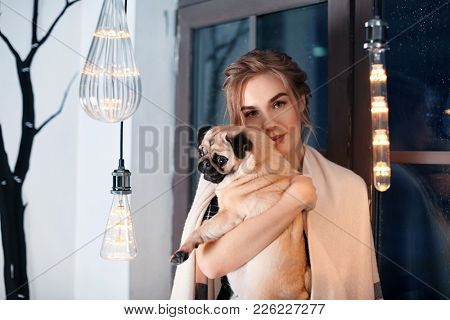 Young woman with cute pug dog near window at home. Pet adoption