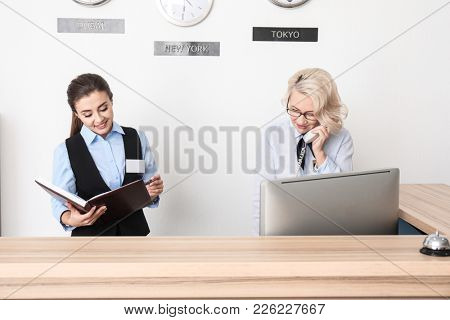 Female receptionist with trainee in hotel