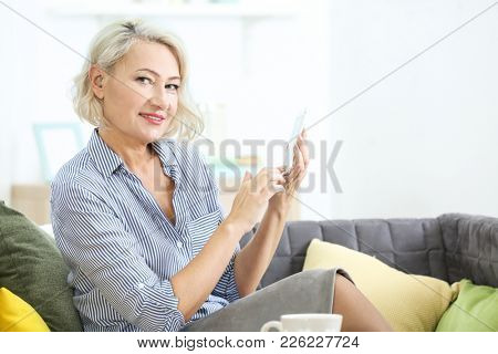 Mature woman with hearing aid using smartphone indoors