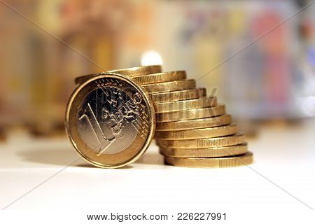 One Euro Coin, Closeup, Twelve Coins Stacked On A Desk With Fifty And Twenty Euro Banknotes Behind