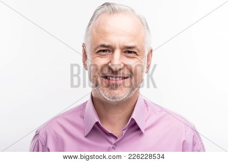 Refined Maturity. The Portrait Of A Handsome Grey-haired Bristled Man In A Lilac Shirt Smiling At Th