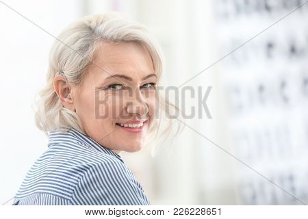 Mature woman with hearing aid indoors