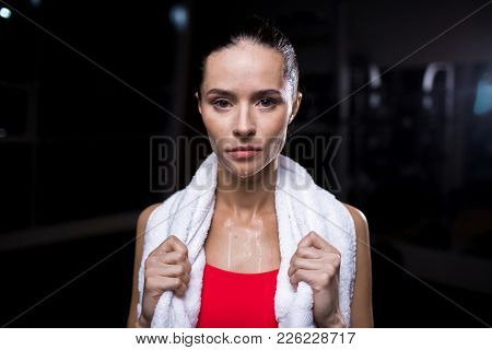 Sweaty sportswoman with white soft towel looking at camera after workout