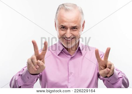 Nice Mood. Handsome Grey-haired Senior Man In A Lilac Shirt Smiling At The Camera And Showing Two V
