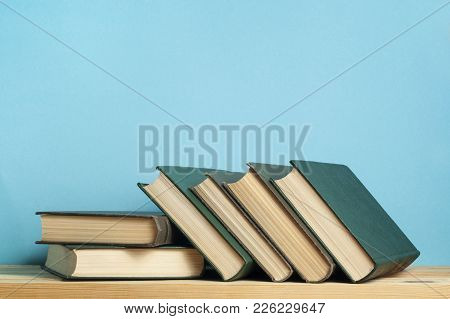 Stack Of Books On Wooden Table On Blue Wall Background. Copy Space For Text Back To School. Educatio