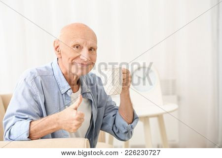 Hearing impaired man with cup of tea showing thumb up gesture at home