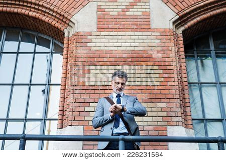 Handsome Mature Businessman Standing In A City, Checking The Time.