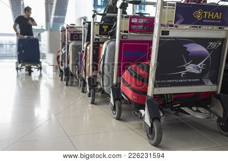 Bangkok, Thailand - June 28, 2015: Stacked Trolleys Loaded With Luggages Against Male Passenger Push