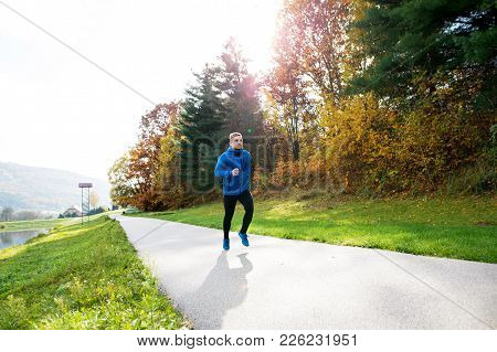 Young Athlete In Blue Jacket Running Outside In Colorful Sunny Autumn Nature. Trail Runner Training