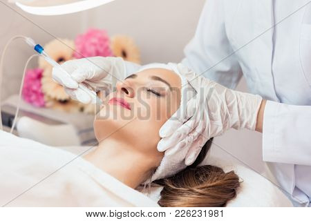 Beautiful woman relaxing during non-invasive facial treatment for rejuvenation in a contemporary beauty center with innovative equipment