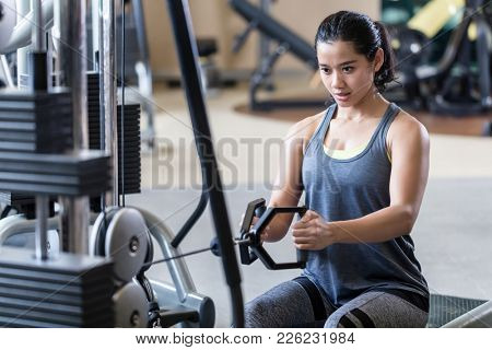 Portrait of a strong and beautiful young woman sitting while rowing at the cable machine for back muscles during intense workout at the gym