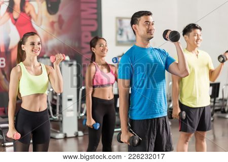 Fit handsome man smiling while exercising alternate bicep curls with dumbbells during group workout class in a modern fitness club