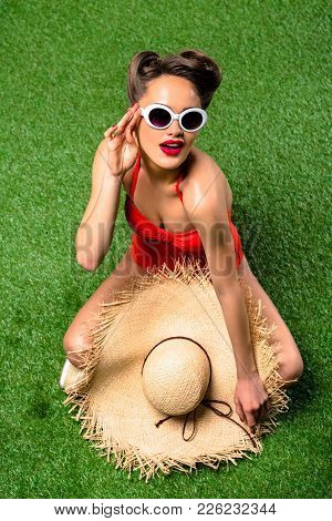 Overhead View Of Beautiful Woman In Swimming Suit With Straw Hat Resting On Green Lawn