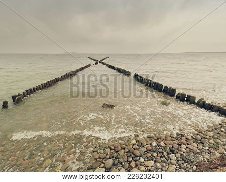 Wooden Breakwater In Wavy Baltic Sea. Evening At Smooth Wavy Sea. Pink Horizon With Low Clouds