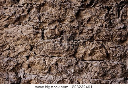 Textured Background Of A Wall Of Medieval Stone Masonry. The Wall Is Sloppy Built Of Mountain Stones