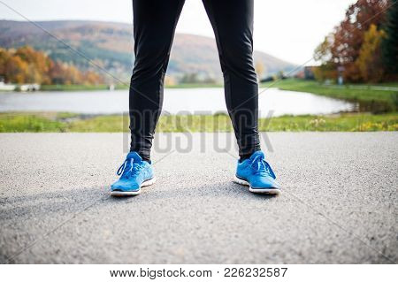 Unrecognizable Young Runner In Blue Jacket Outside In Colorful Sunny Autumn Nature Standing On An As