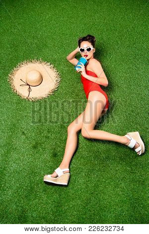 Overhead View Of Stylish Young Woman In Swimming Suit With Drink Lying On Green Grass