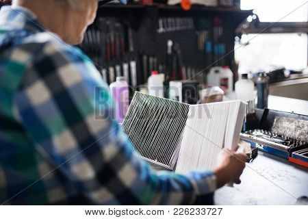 Female Mechanic Repairing A Car. An Unrecognizable Senior Woman Working In A Garage.