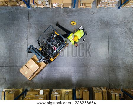An Accident In A Warehouse. Woman Performing Cardiopulmonary Resuscitation. Aerial View.