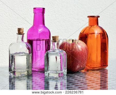 Four Vintage Glass Bottles With Apple Cider Vinegar And Ripe Red Apple Against A High Key Background